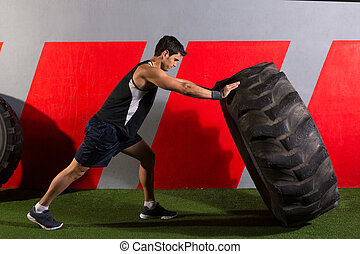 man flipping a tractor tire workout gym exercise - man...
