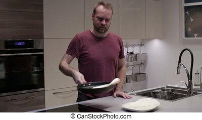 Man flips pancakes in a frying pan