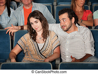Man Flirting in Theater - Man flirts with young woman in...