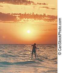 Man floating on a SUP board in the sea at sunset.