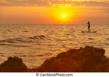Man floating on paddle board in sea at sunset.