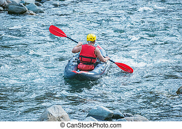 Man floats by inflatable boat on the mountain river.
