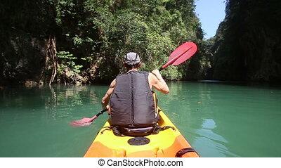 man floats kayak and looks around kayak