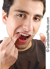 Man flossing his teeth - young man flossing his teeth...