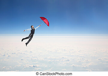 Man flying in the sky with umbrella