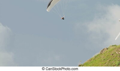 Man flying on a paraglider over a Windmill viewpoint on...
