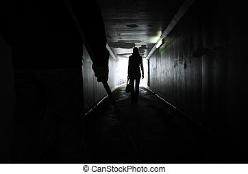 Man follows a young woman in a dark tunnel - Silhouette of a...