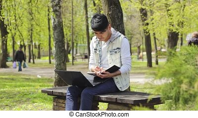 Man freelancer working in laptop in the park