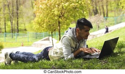Man freelancer working on laptop and lying down on the grass...