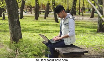 Man freelancer working on laptop in the park