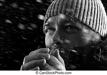 Man freezing in snow storm BW - Freezing cold man standing...