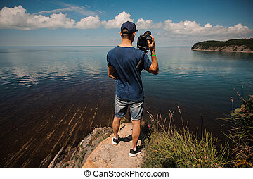 man from behind photographing lake