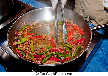 Man Frying Food - Man frying bacon and peppers in a pan with...