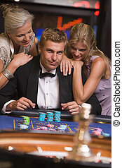 Man gambling in casino surrounded by attractive women - Man...