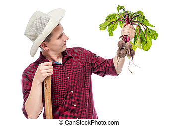 Man gardener with a bunch of beets in his hand on a white background