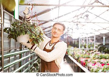 Man gardener working and hanging flowers in pots