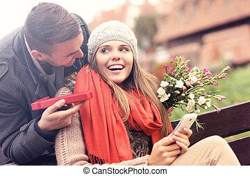 man, ge sig, överraskning, gåva, till, kvinna, i parken