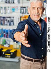 Man Gesturing Handshake In Hardware Store
