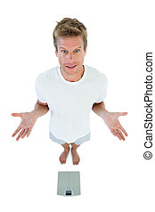 Man gesturing in front of a weighing scale