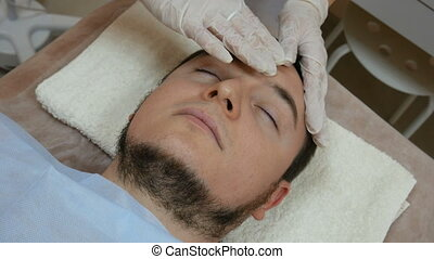 Man getting a face massage before mask