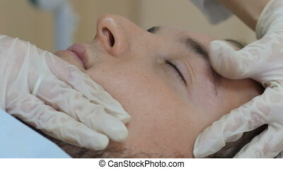 Man getting a face massage in clinic. cosmetologist concept.