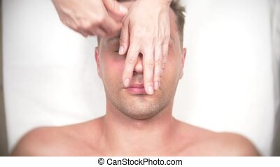 Man getting a face massage. Massage the face and neck. lying...