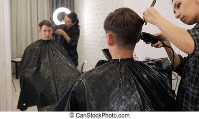 Man getting a haircut by a hairdresser. - Man getting a...