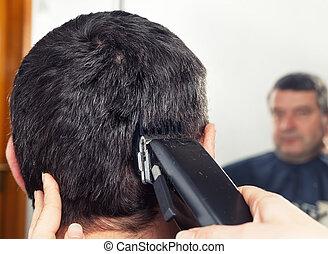 barber making haircut to man