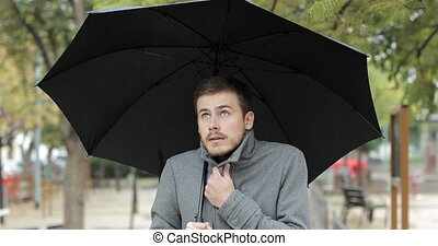 Man getting cold in a rainy day walking in a park - Front...