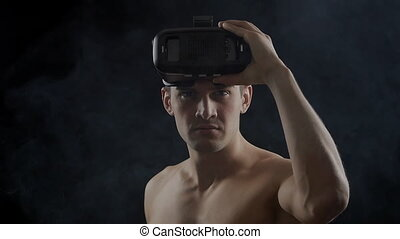 man getting experience using VR-headset, standing in dark, with smoke around him.