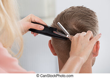 Man Getting Haircut From Female Hairdresser At Salon