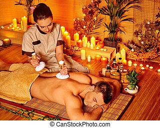 Man getting herbal ball massage treatments . - Man getting...