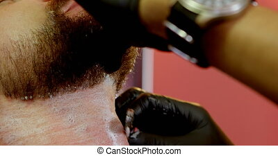 Man getting his beard shaved with razor 4k - Barber applying...