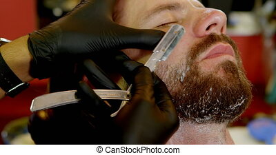 Man getting his beard shaved with razor 4k