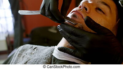Man getting his beard shaved with straight razor 4k