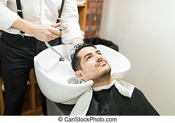 Man Getting His Hair Washed By Barber In Salon