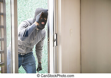 Man getting ready to rob a house