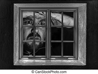 Man giant looking through a window at night