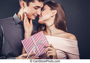 Man gives a gift box to his girlfriend for Valentines day.