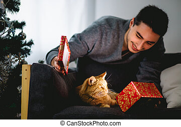 man gives a gift to the red cat