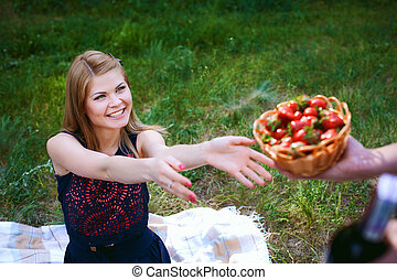 man gives a girl a basket with strawberries