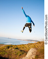 Man giving a big jump while practicing trail running