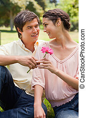 Man giving a flower to a woman