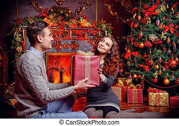 man giving a gift - Happy young people give each other gifts...