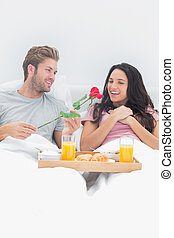 Man giving a rose to his wife during breakfast in bed