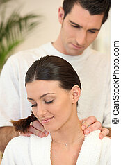 Man giving a young woman a shoulder massage