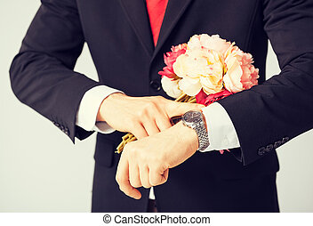 man giving bouquet of flowers - close up of young man giving...