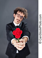Man giving fabric rose - Boy with glasses is donating a...
