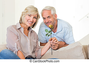 Man giving flower to a smiling woman sitting on couch