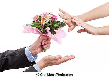 Man giving flowers to his wife after argument